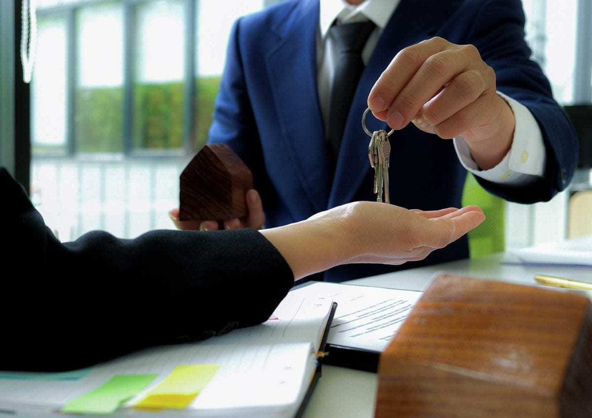 Man in suit handing over keys to home owner illustrating buying a home through a private mortgage broker