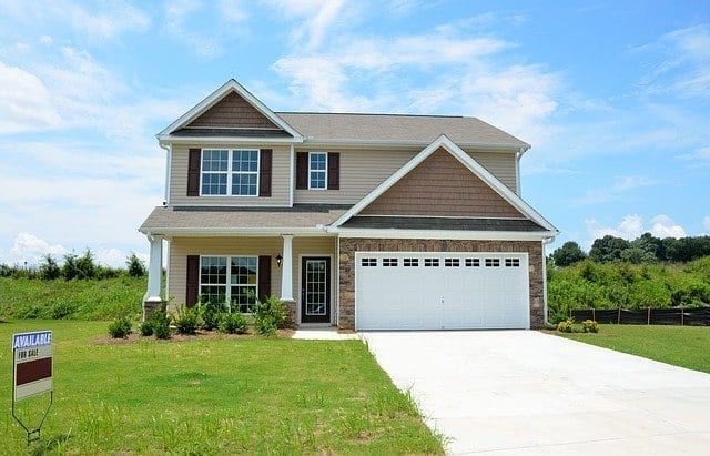 New double-story home with for sale sign, to be purchased with a private mortgage