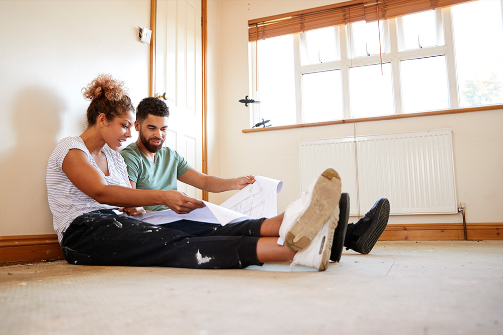 Couple of first time homebuyers sitting on the floor of their new home, with closing costs calculated into their budget