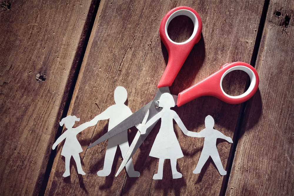 Scissors cutting through a paper family alluding to family divorce or separation