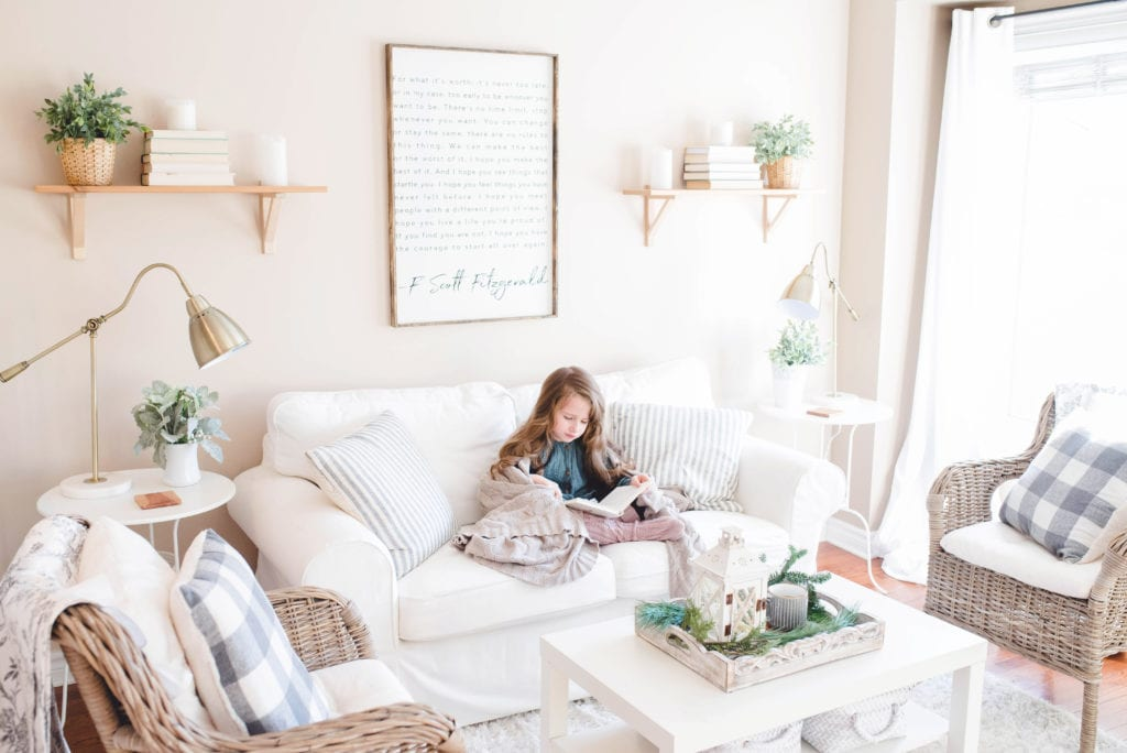 A young girl sitting a couch reading in a nicely decorated home, highlighting the chance to keep your existing family home when going through separation or divorce