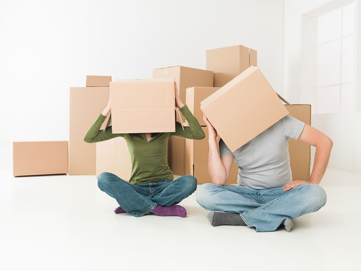Couple with boxes on their heads sitting on floor in their new house, feeling stressed; highlighting the stress relief that Kelowna Mortgage Broker can provide in homebuying