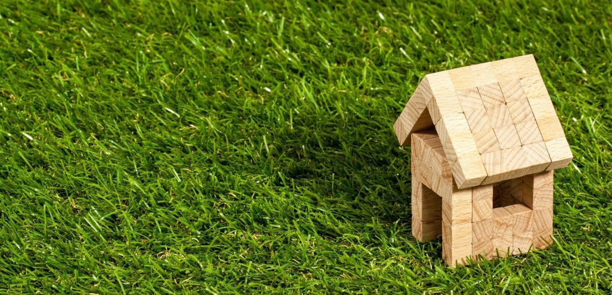 A miniature wooden house on grass highlighting mortgage appraisal in kelowna
