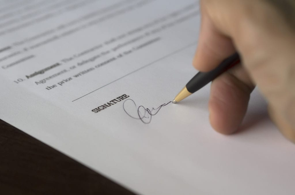 Hand signing a mortgage renewal document; automatically signing without looking at options is a common mortgage mistake