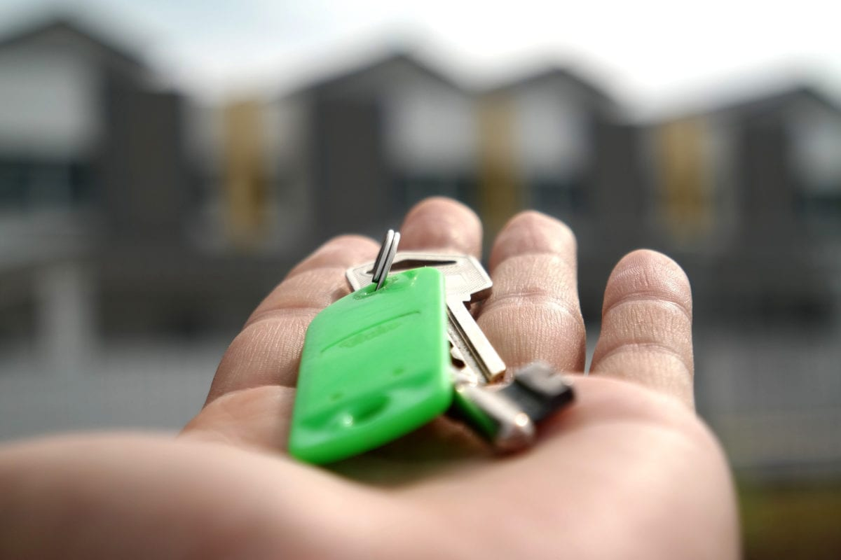 Closeup of hand holding new house keys; highlighting the importance of a homebuying team