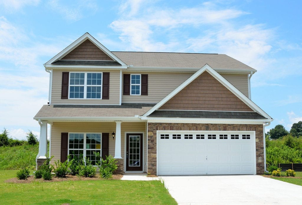 new house for sale upon passing a mortgage stress test; blue sky background and green grass, beige colouring two floors with garage and big windows
