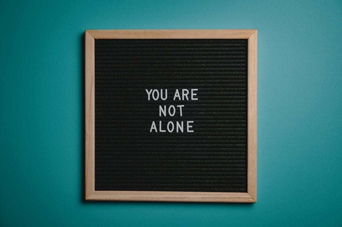 letter board on a turquoise wall that read 'you are not alone', alluding to missing mortgage payments due to the covid-19 pandemic
