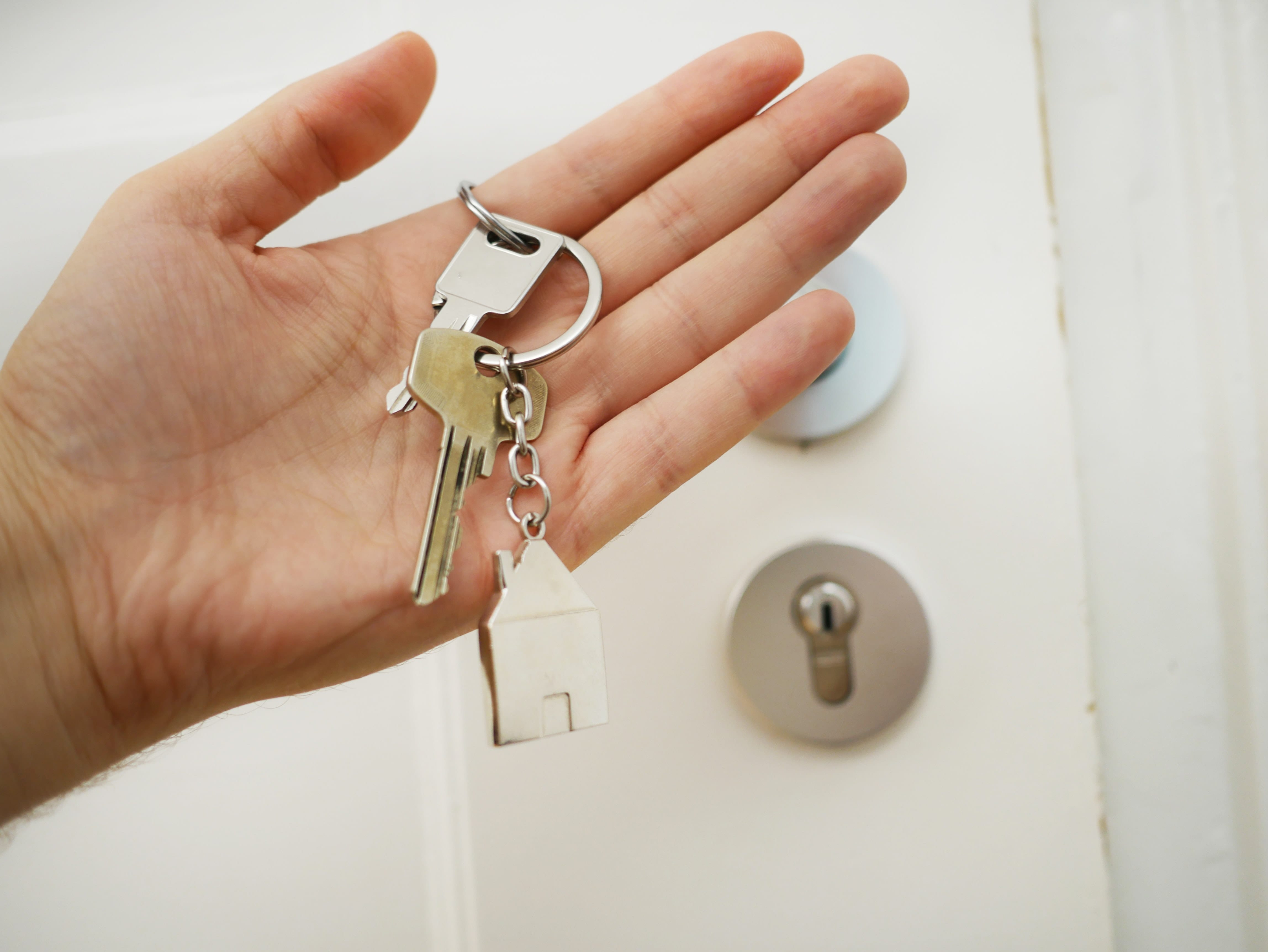 Closeup of a hand holding a set of keys with a silver house keychain, highlighting the choice of securing a mortgage with a mortgage broker or bank
