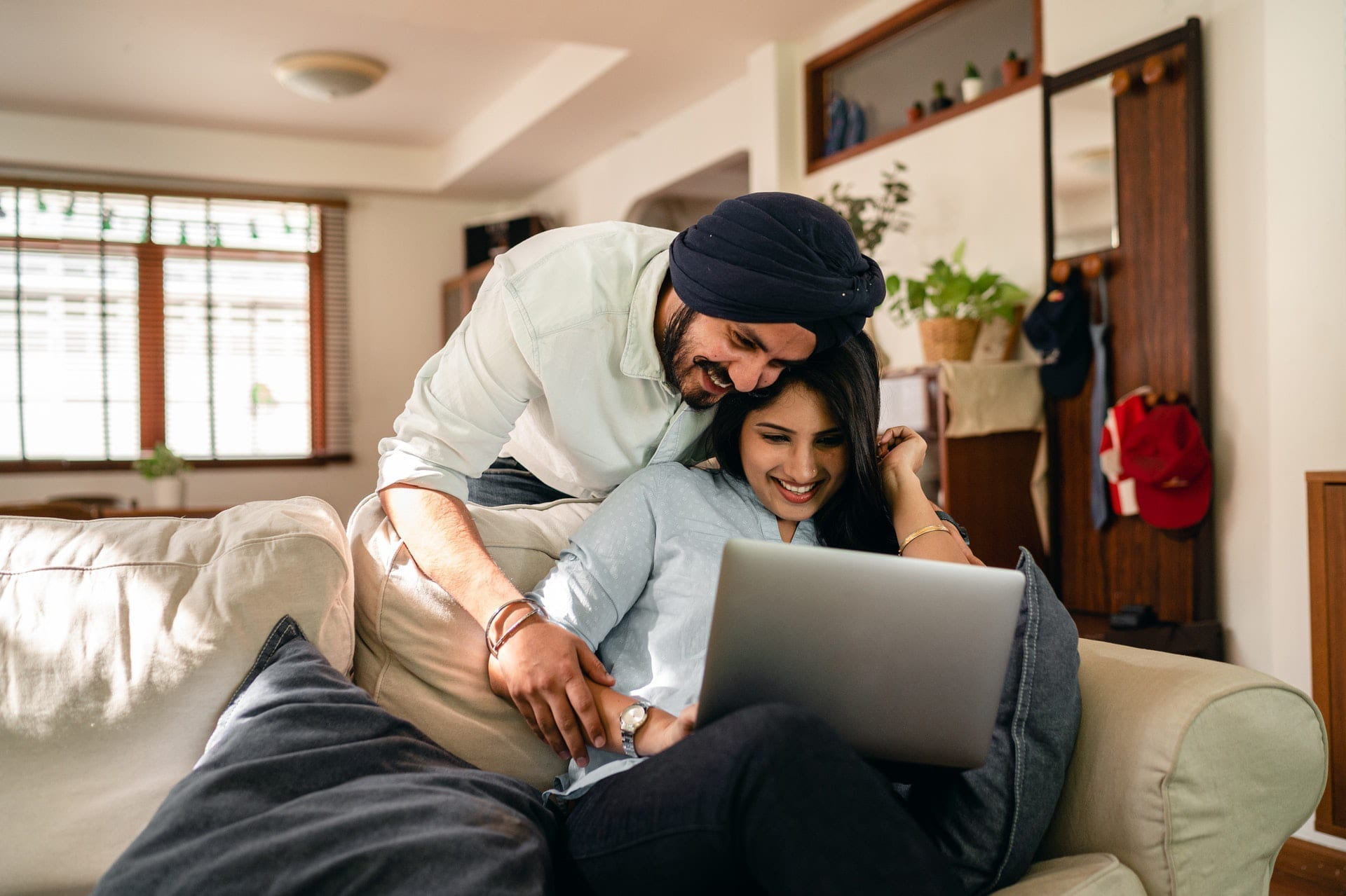 Ethnic couple smiling and looking at laptop in a beautiful home, securing a mortgage post covid-19